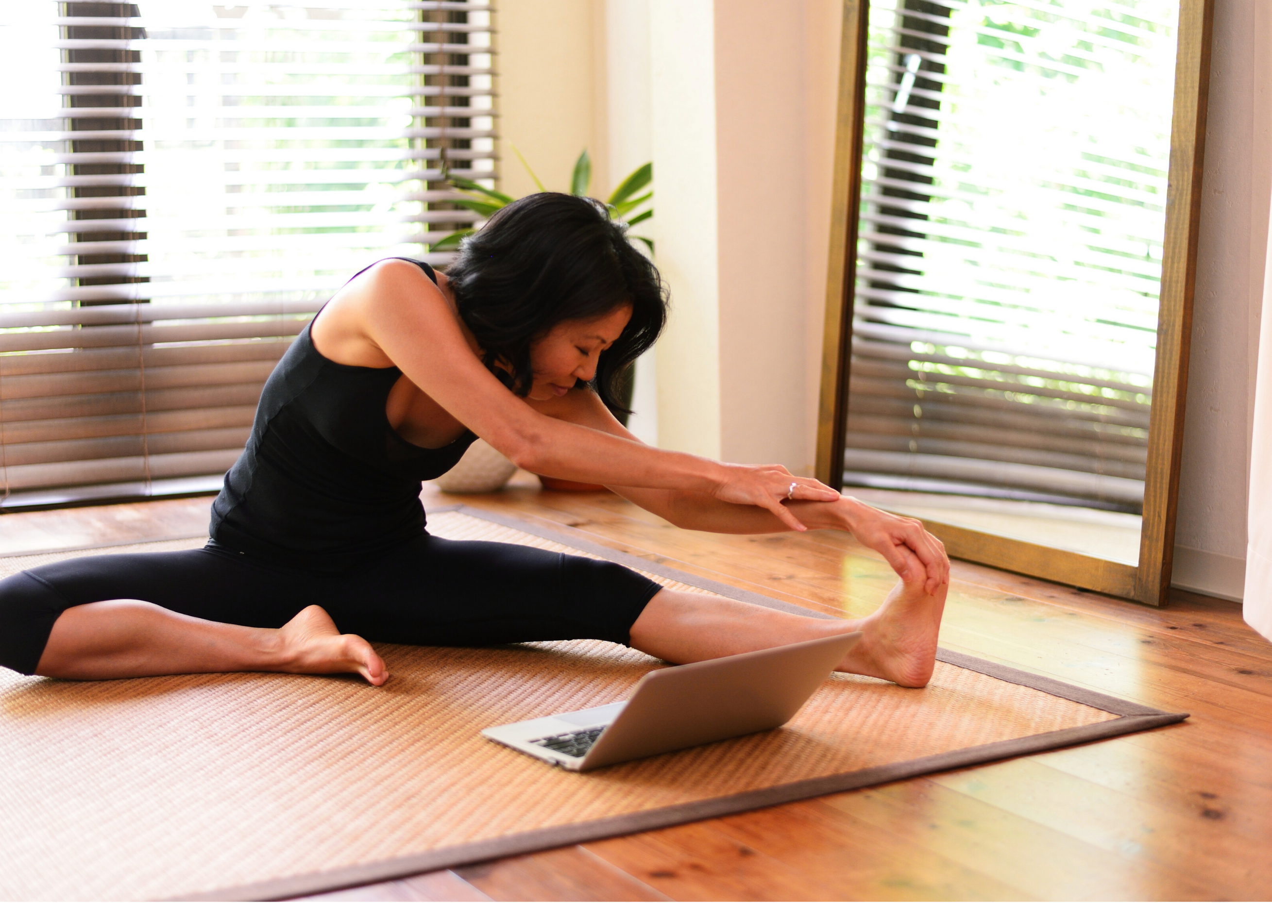 woman wearing gym clothes doing stretch exercise on the floor in front of a computer